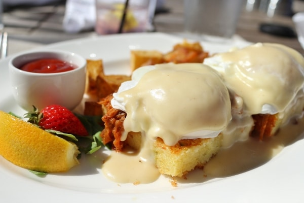 a closeup of Eggs Benedict on square pieces of cornbread with pulled pork