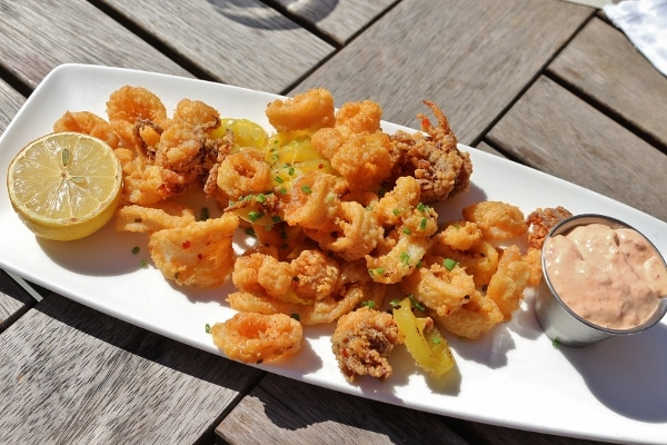 a white platter topped with fried calamari with sliced banana peppers