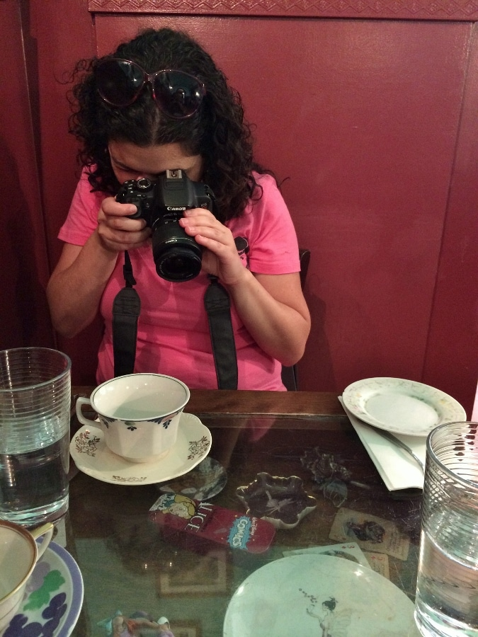 A woman taking a photo of a cup and saucer on a table