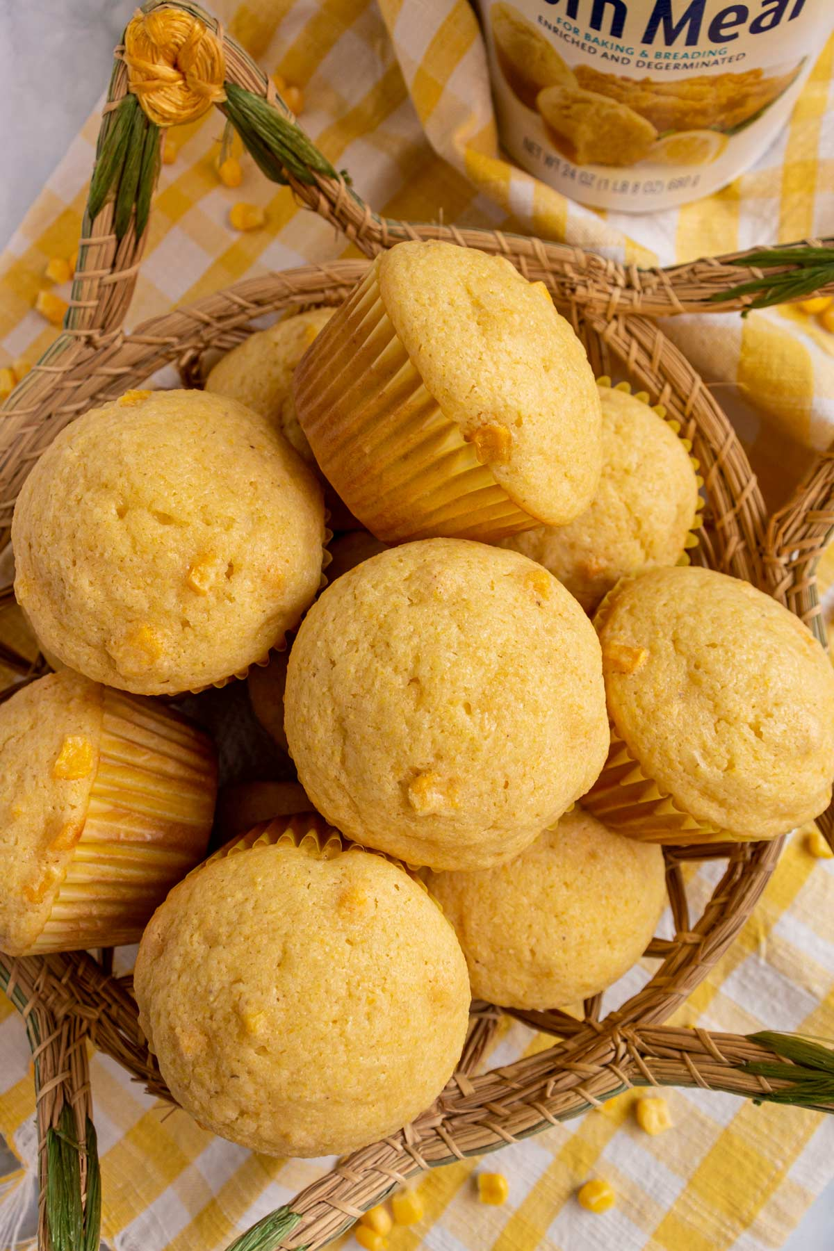 A basket of corn muffins on a yellow and white gingham towel.