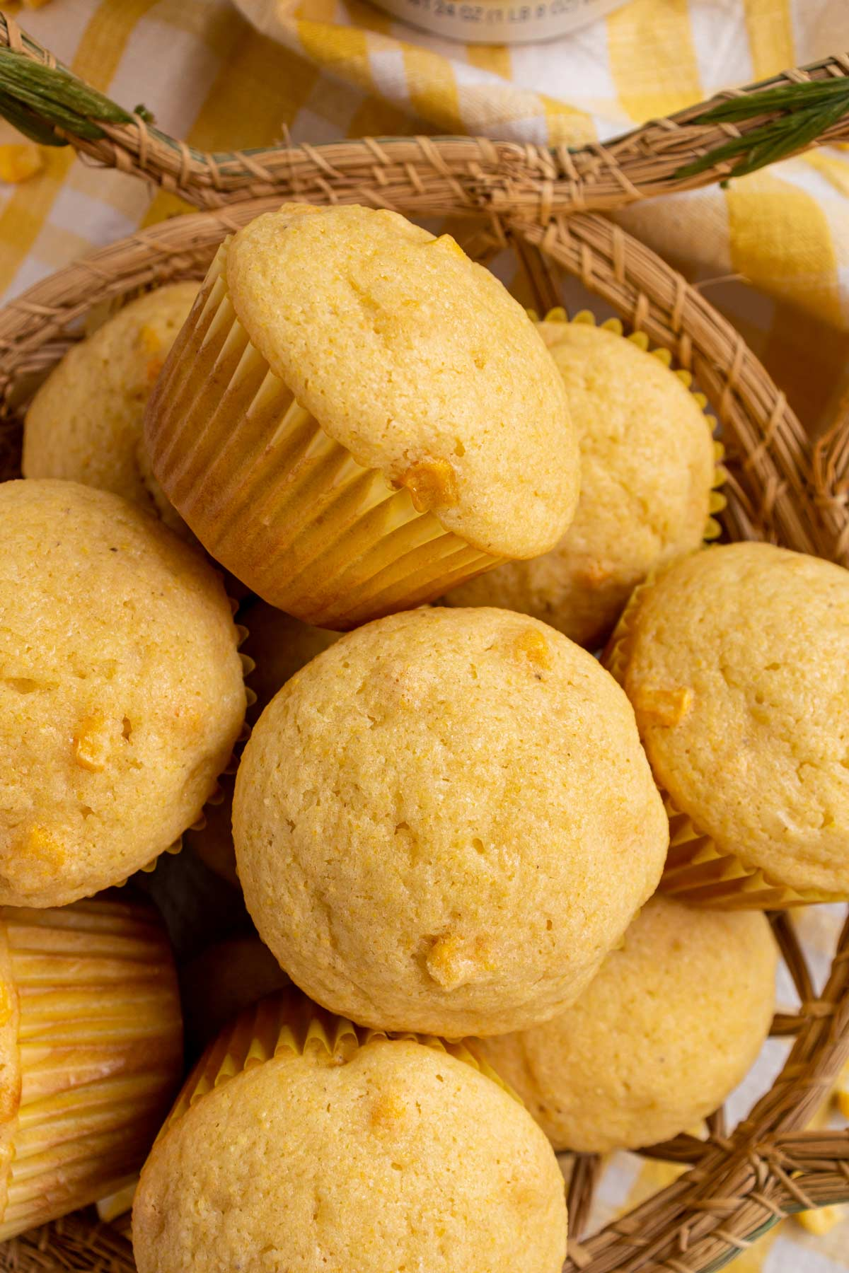 A closeup of corn muffins with yellow paper liners in a basket.