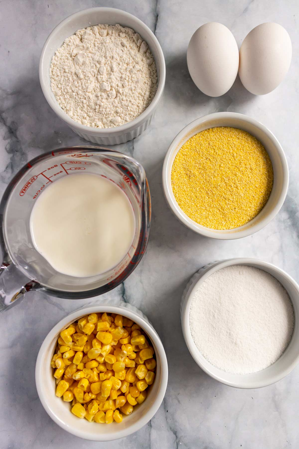 Flour, eggs, milk, cornmeal, sugar, and corn on a marble background.