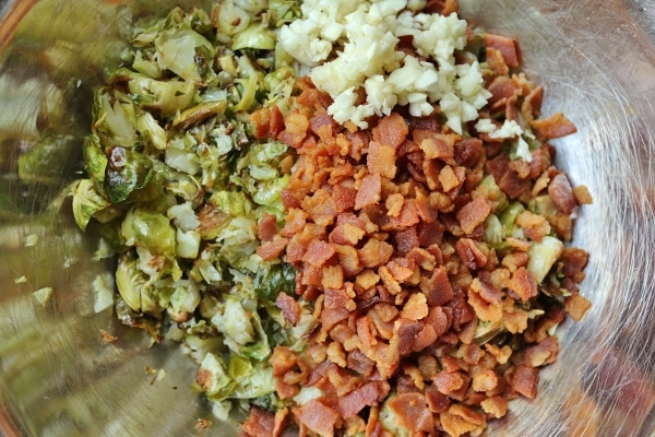 a mixing bowl filled with chopped cooked brussels sprouts and crispy crumbled bacon