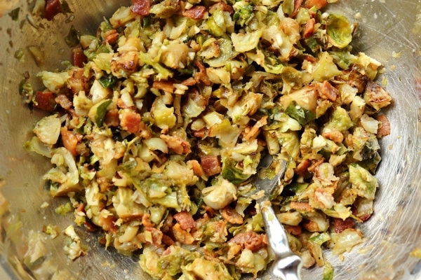 a mixture of chopped brussels sprouts and bacon in a metal mixing bowl