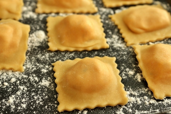 A closeup of homemade raviolis on a flour-dusted black surface