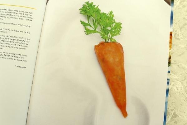 a dumpling shaped like a carrot on a white surface