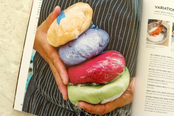 two hands holding plastic wrapped balls of dough in different colors