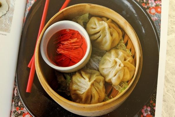 three large soup dumplings in a bamboo steamer basket