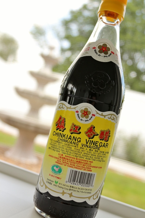 A close up of a bottle of Chinkiang black vinegar with a yellow label