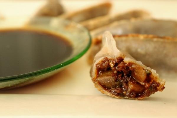 a half-eaten dumpling with a dark brown filling next to a green dipping sauce bowl