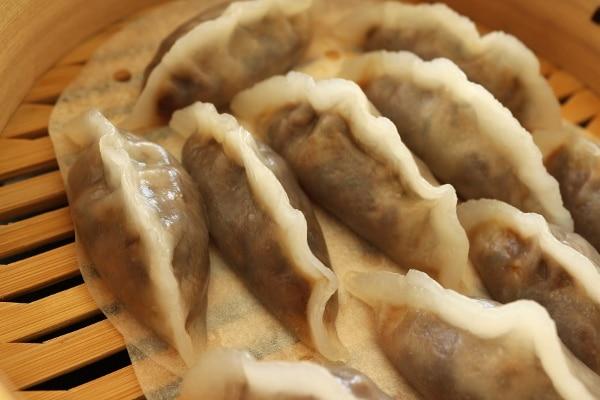 a closeup of steamed dumplings in a bamboo steamer basket