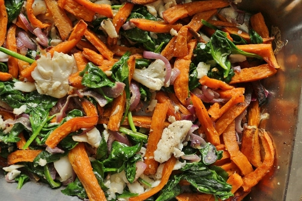A pile of sweet potato fries mixed with cooked fish, spinach, and red onions