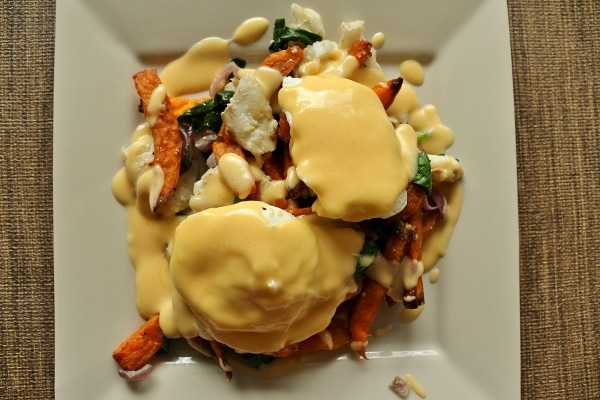 a white square plate topped with fish hash, poached eggs, and Hollandaise sauce