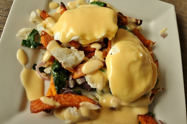poached eggs with Hollandaise sauce on top of fish hash with spinach and sweet potatoes