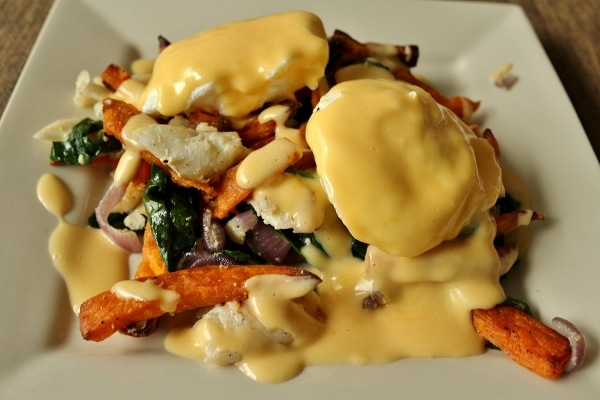 A plate of sweet potato fries and fish hash with eggs and Hollandaise sauce on top