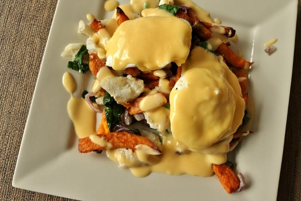 overhead view of a square plate topped with fish hash, eggs, and Hollandaise sauce