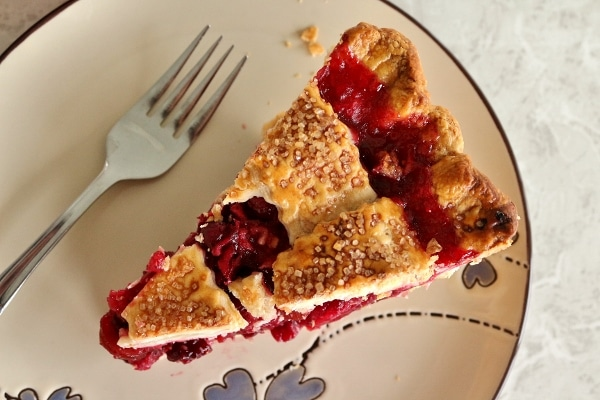 overhead view of a slice of cranberry pie with a lattice crust on a plate