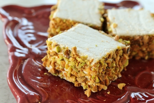 A closeup of a square marshmallow coated in pistachios on a dark red plate