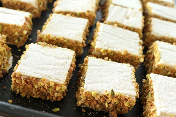 a black tray topped with square marshmallows with chopped pistachios around the edges