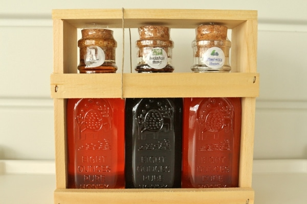 three glass jars of honey in a wooden box