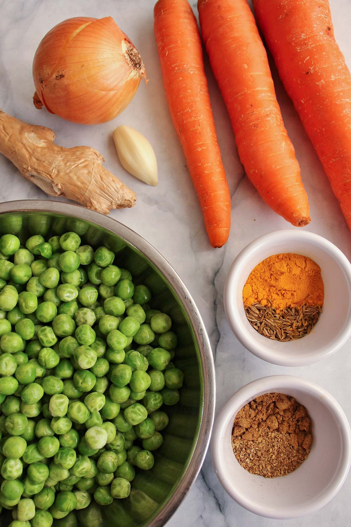 Onion, ginger, garlic, carrots, peas, and spices on a white marble surface.