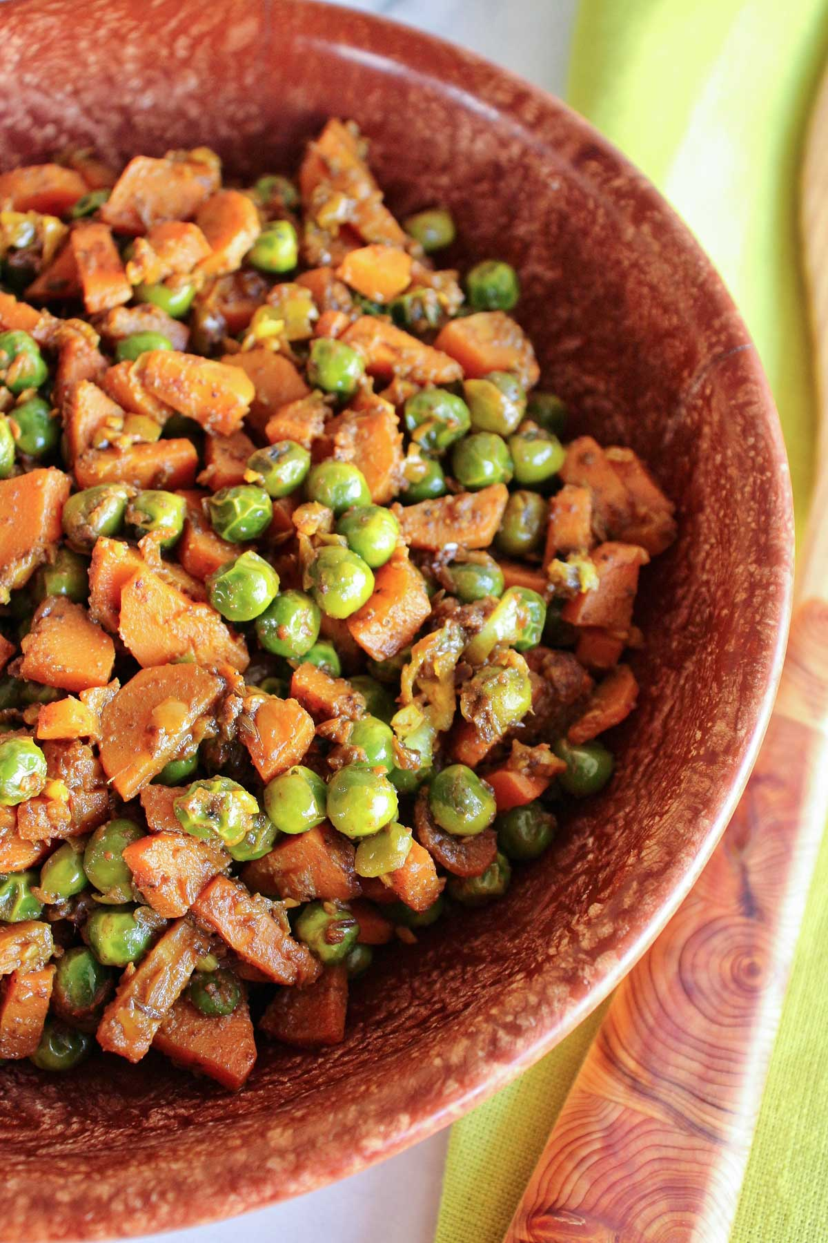 Closeup of Indian carrots and peas in a rustic brown bowl.