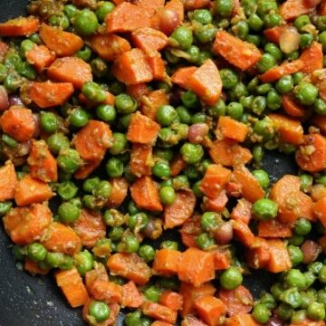 overhead view of cooked carrots and peas in a nonstick skillet