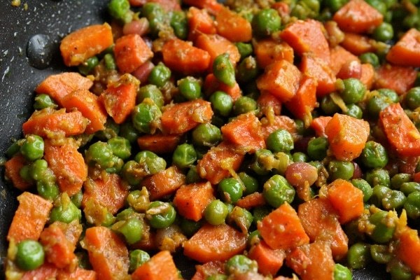 a closeup of cooked carrots and peas in a skillet