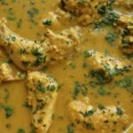 overhead view of chicken pieces cooked in a red lentil curry sauce in a pan
