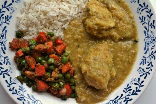 overhead view of a shallow white bowl with chicken curry, basmati rice, peas and carrots