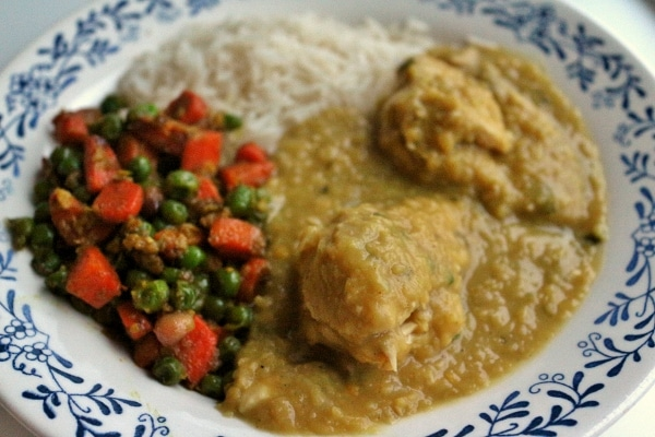 side view of a white and blue bowl with chicken curry, rice, peas and carrots
