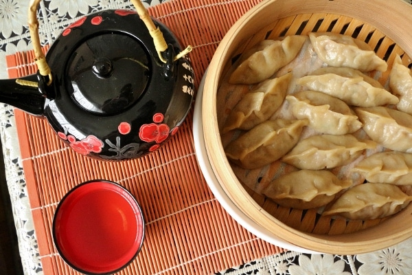overhead view of a black teapot, tea cup, and bamboo steamer basket of dumplings