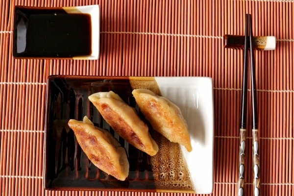 overhead view of fried dumplings on a rectangular plate with sauce and chopsticks on the side