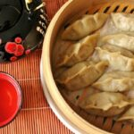 Pork and cabbage dumplings in steamer basket with tea pot and tea cup