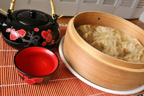 side view of a black teapot next to a bamboo steamer basket filled with dumplings