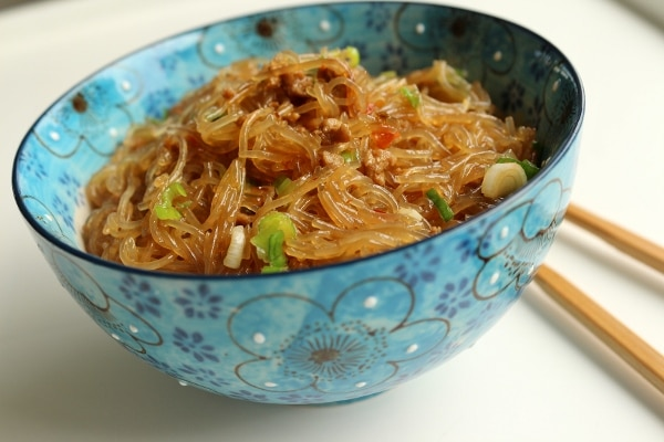 side view of a blue bowl filled with cellophane noodles with ground meat and scallions