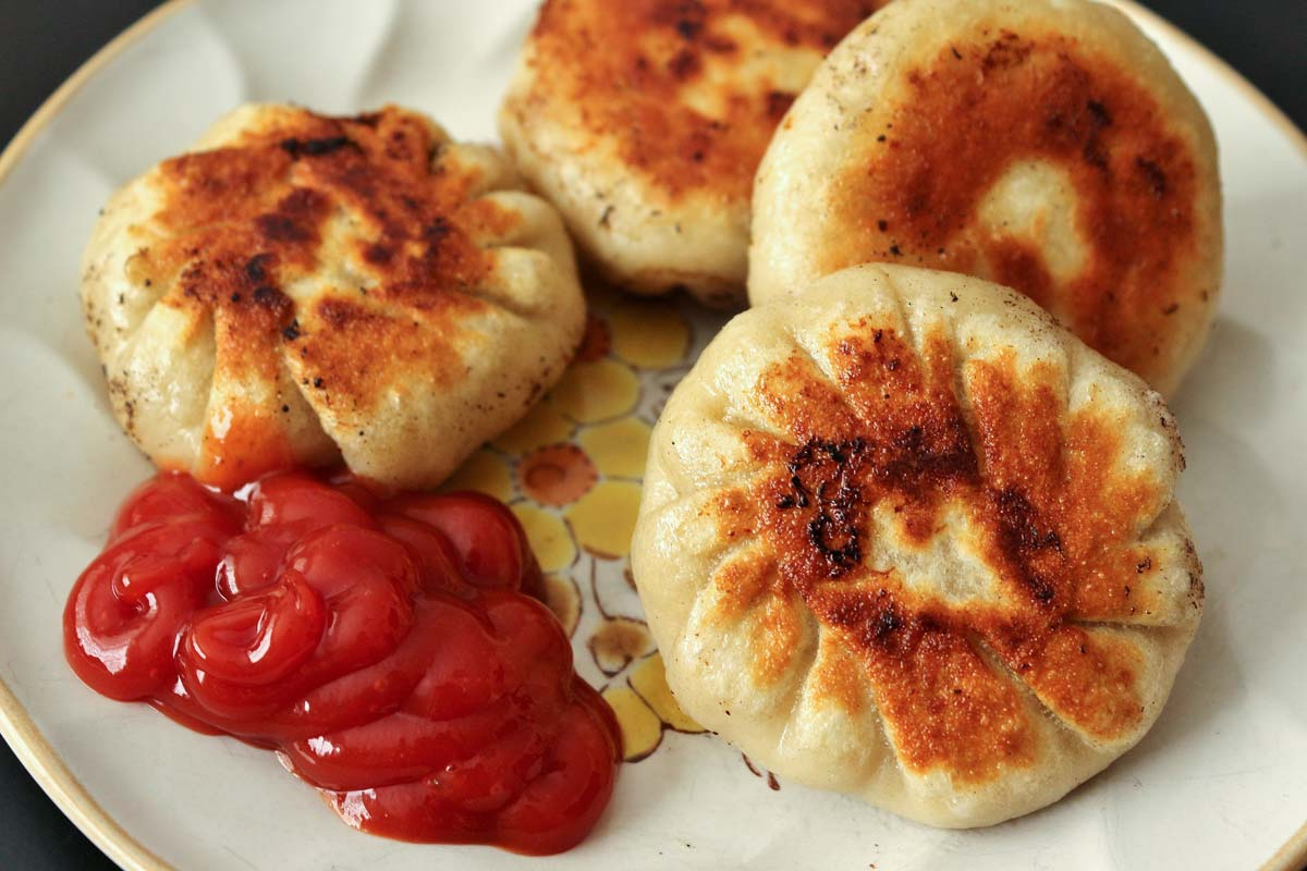 A plate of round pan-fried dumplings with ketchup on the side.