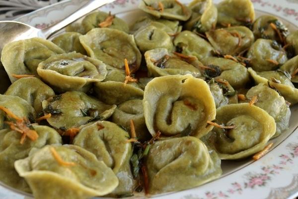 a platter of green tortellini-shaped dumplings