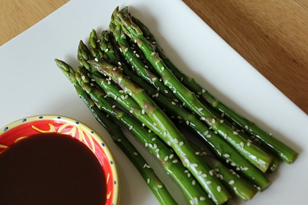 overhead view of asparagus topped with sesame seeds on a white plate