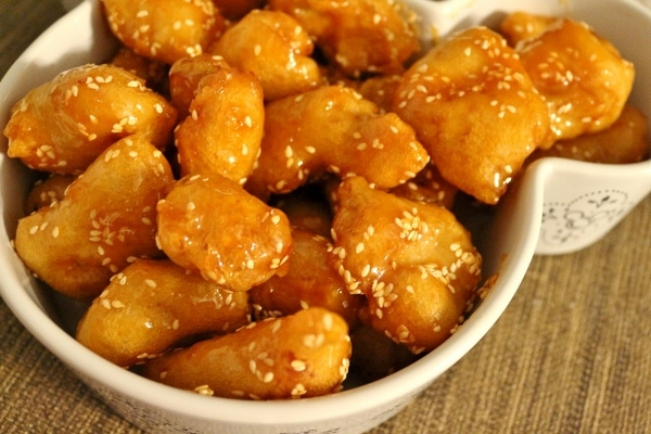crispy fried sesame chicken pieces in a white serving dish