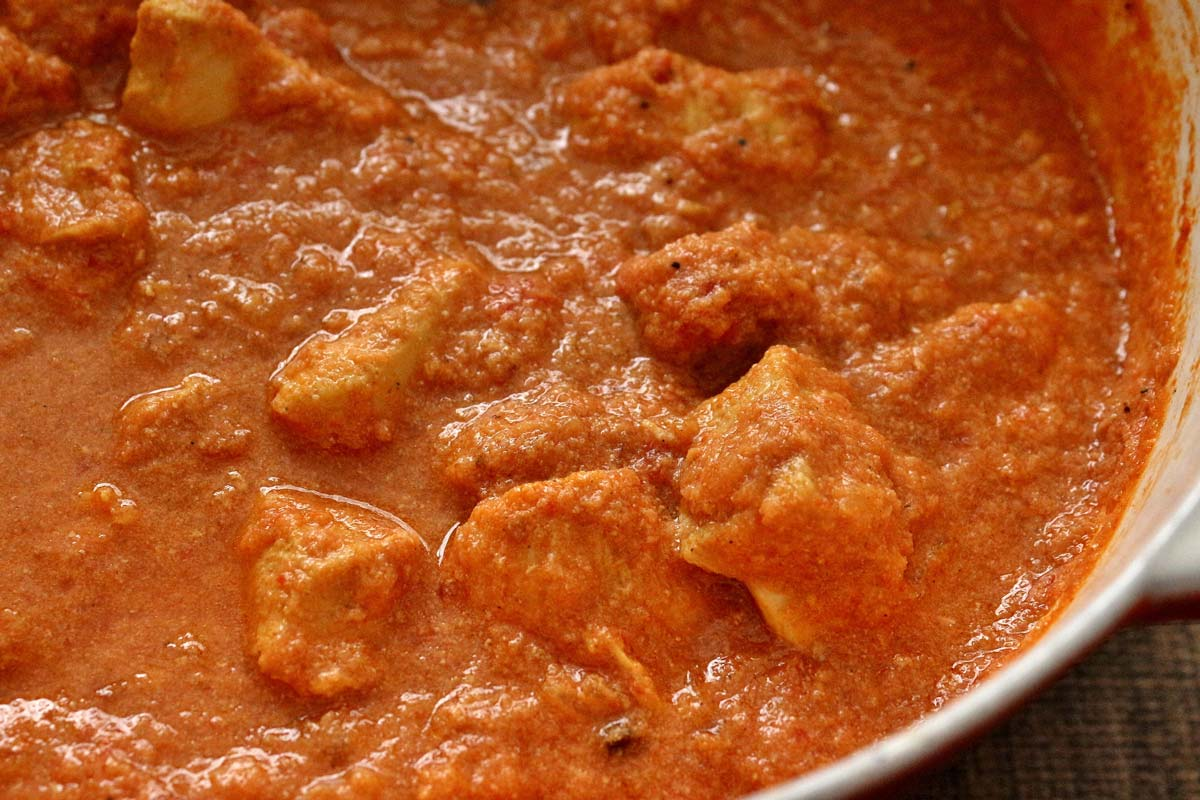Closeup of chicken pieces in a creamy tomato curry sauce.
