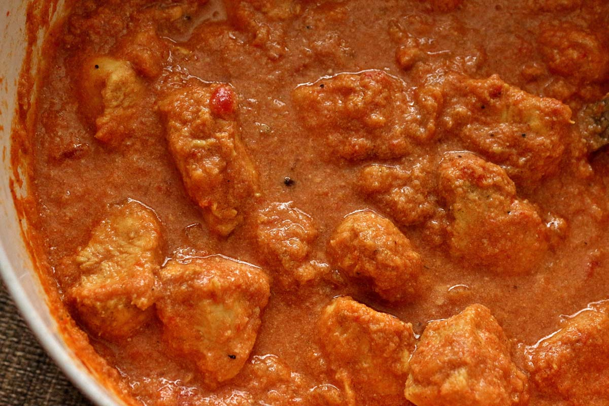 A pot of Indian curry with chicken and a creamy tomato sauce.