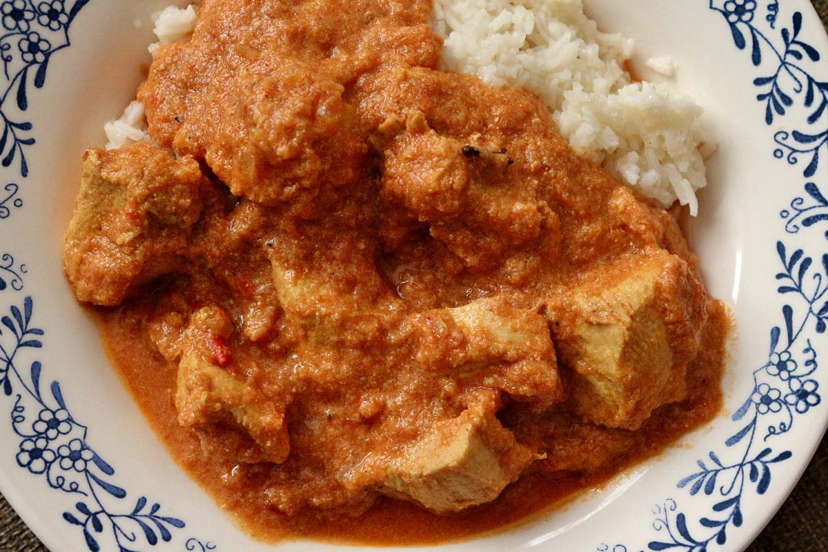 Chicken curry in creamy tomato sauce served with white rice in a shallow bowl.