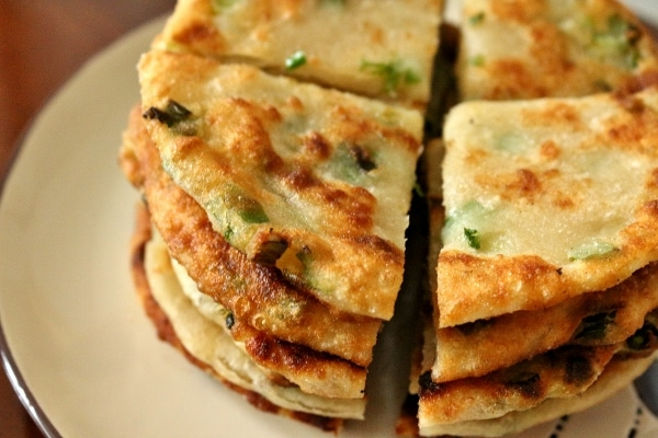 a stack of fried scallion pancakes cut into quarters on a plate