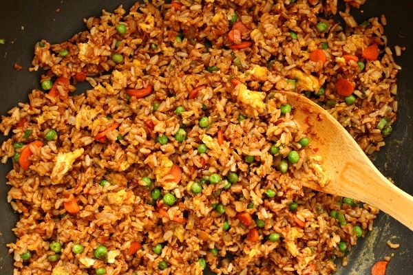 vegetable fried rice in a wok with a wooden spoon