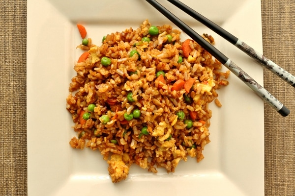 overhead view of fried rice with vegetables on a square plate with chopsticks on one corner