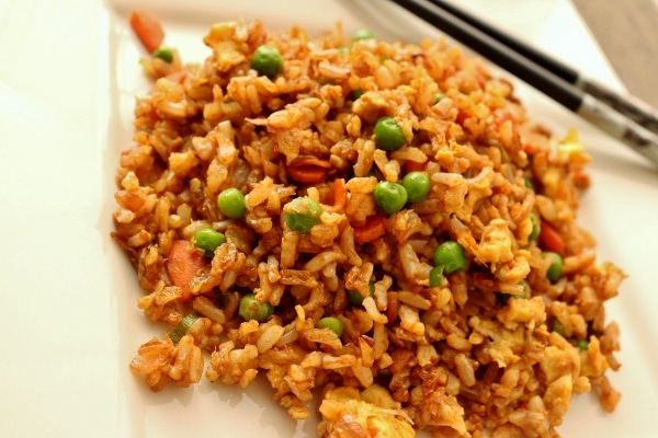 a closeup of a plate of vegetable fried rice with peas and carrots