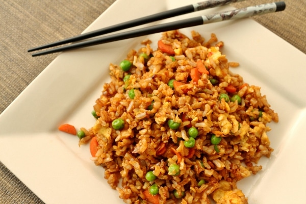 vegetable fried rice on a square plate with chopsticks on one corner