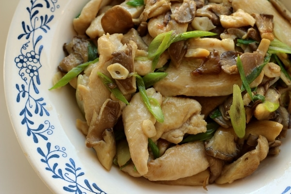 overhead view of a shallow bowl of stir-fried chicken with mushrooms and scallions