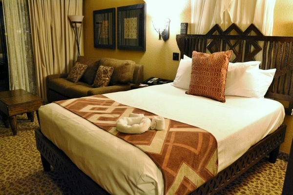 A hotel room with a large bed and sitting area